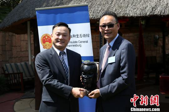 全非洲中国和平统一促进会会长李新铸(右)代表南非华人社区向杨培栋副总领事赠送纪念品。 宋方灿 摄