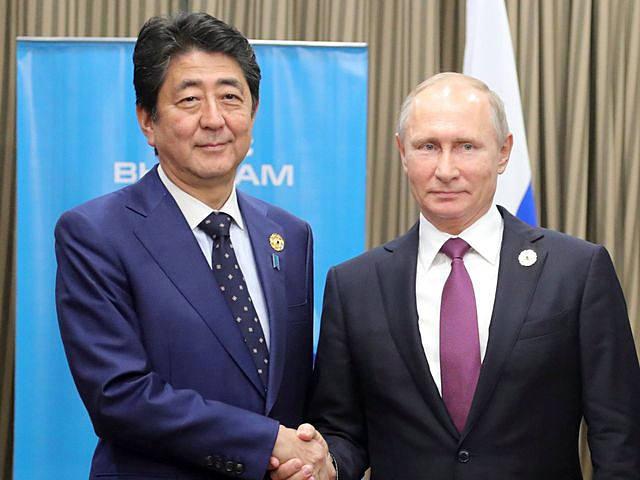 普京(右)与安倍握手。(新华/路透)