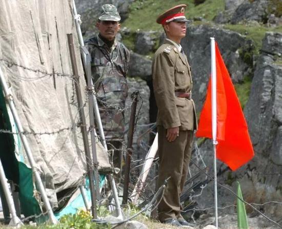▲资料图片:在中印边境乃堆拉山口,一名中国边防军人(右)与一名印度边防军人隔着边界的铁丝网值勤。