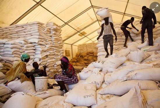 ▲在南苏丹的世界粮食计划署分发点,男人们负责扛食物,女人们等着分发食物。图据路透社