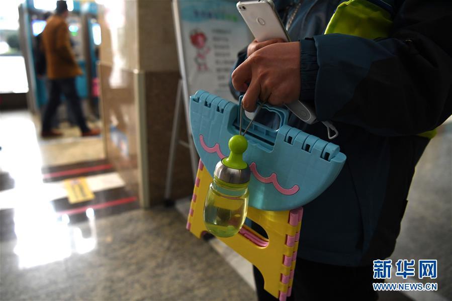 杨召伟在合肥一家医院的自助挂号机前为怀二宝的爱人挂到了妇产科号,板凳、水杯、手机充电宝是他每次排队的必备物品(11月23日摄)。新华社记者 刘军喜 摄