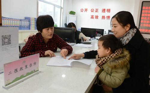 """资料图片:社区工作人员(左)为居民介绍""""全面二孩""""政策(2016年1月14日摄)。新华社记者 王晓 摄"""