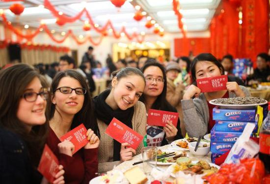 在华外国留学生们手拿红包在学校食堂过年。新华社