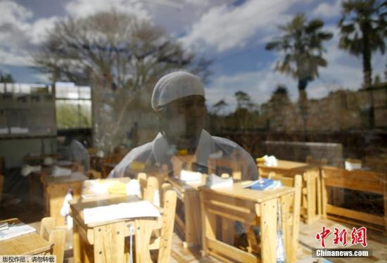 资料图:2016年2月14日,日本福岛,东京电力公司福岛第一核电站附近的禁区里,50岁的木村先生站在小女儿由奈以前上学的教室前。他在五年前的海啸中失去了父亲、妻子和大女儿,小女儿也失踪了。