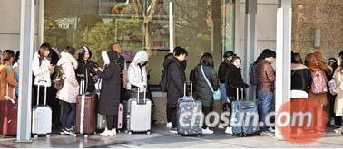 """3月23日上午6点,在首尔中区乐天免税店前,约300名中国""""代购""""正在排队等待免税店营业。(韩国《朝鲜日报》网站)"""