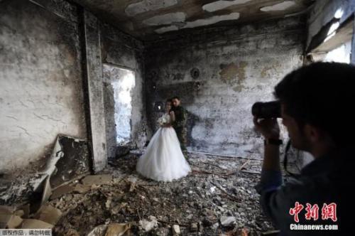 叙利亚霍姆斯一对新婚夫妇以饱受战争蹂躏被毁的建筑为背景拍摄了婚纱照。