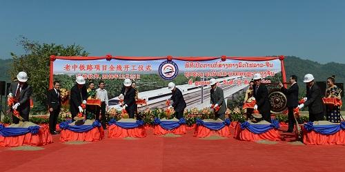 2016年12月25日,中国老挝铁路全线开工仪式在老挝北部琅勃拉邦举行。老挝总理通伦率老中双方代表挥铲破土,并亲自鸣锣九响。 新华社发