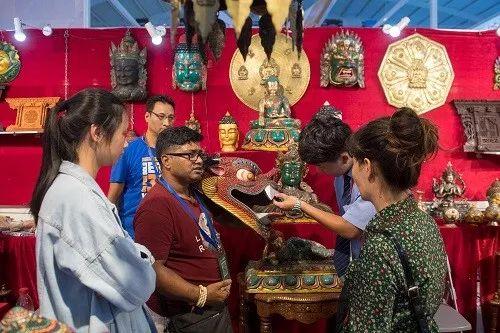 ▲来自尼泊尔的客商(左三)在第5届中国-南亚博览会上出售特色手工艺品。