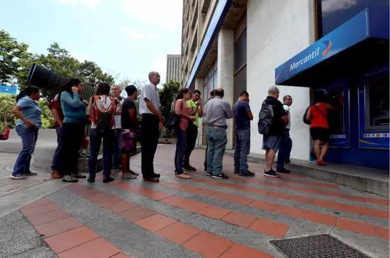 8月20日,在委内瑞拉首都加拉加斯,人们在ATM机前排队取钱。新华社发(格雷戈里奥·特兰摄)