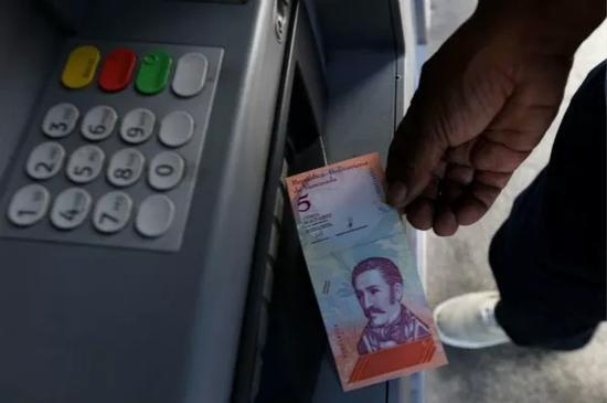 """8月20日,在委内瑞拉首都加拉加斯,一名男子从ATM机中取出一张新货币""""主权玻利瓦尔""""。新华社发(格雷戈里奥·特兰摄)"""