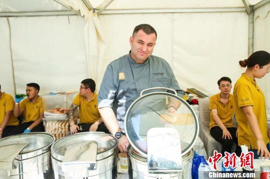 """南非驻华大使馆7日至8日举行""""开放日""""活动,超过两千名中国民众走进使馆感受丰富多彩的南非文化。图为南非大厨现场烹饪特色美食。 南非驻华大使馆供图 摄"""