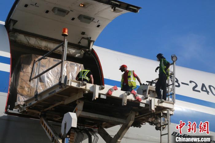 图为工作人员5日在紧张运送物资进入货舱。 王曦 摄