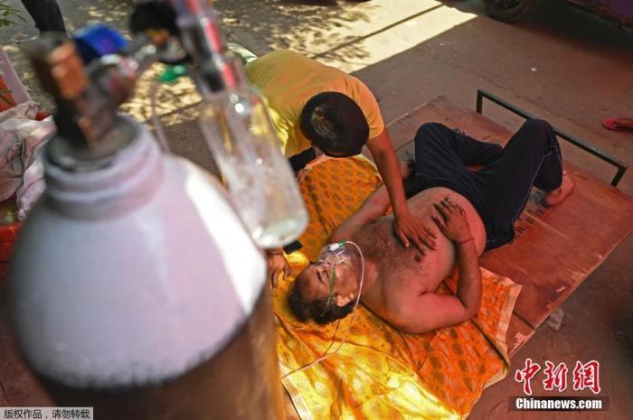 当地时间4月26日,印度加兹阿巴德,一名新冠患者在路边搭建的帐篷内吸氧。