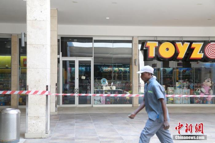 """当地时间4日1日,南非约翰内斯堡,关闭的玩具店前已经拉起警戒线,只有个别建筑工人从外面经过。受疫情影响,南非已经实施全国范围""""封城""""。 <a target='_blank' href='http://www.chinanews.com/' _fcksavedurl='http://www.chinanews.com/'>中新社</a>记者 王曦 摄"""