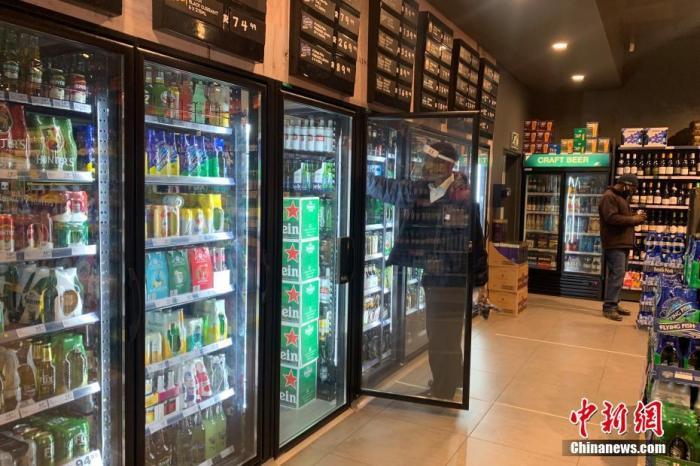当地时间7月22日,南非约翰内斯堡,一家酒类商店的店员佩戴面罩整理冰箱内的货物。 <a target='_blank'  data-cke-saved-href='http://www.chinanews.com/' href='http://www.chinanews.com/'>中新社</a>记者 王曦 摄