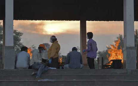 People are seen next to burning pyres of victims who lost their lives due to the COVID-19 coronavirus at an open crematorium in Bangalore, India, on 26 April 2021. Picture: Manjunath Kiran/AFP